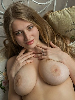 """An uninhibited view of Sheela A's magnificent large breasts with puffy nipples, shapely hips, and pink, moist pussy as she sprawls inviting"